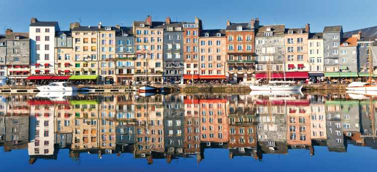 Colourful row of houses reflected in water | Honfleur | Riviera Travel | Escorted Tour