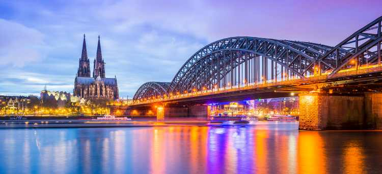Illuminated Cologne cathedral and bridge over the river during the evening | Cologne, Germany