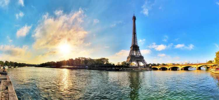 The Eiffel Tower in the evening sun on the banks of the Seine river in Paris, France