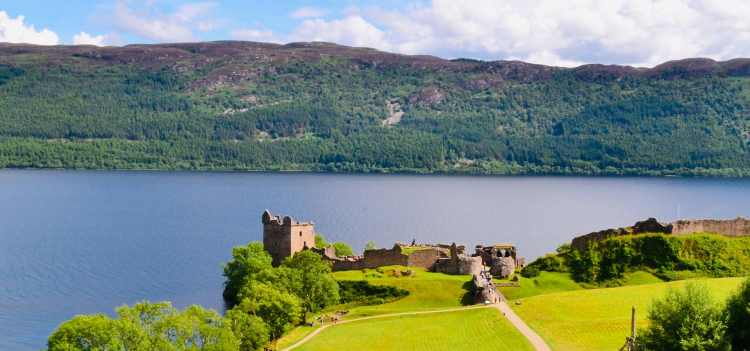 Green fields surrounding Urquhart Castle at Loch Ness | World Voyager