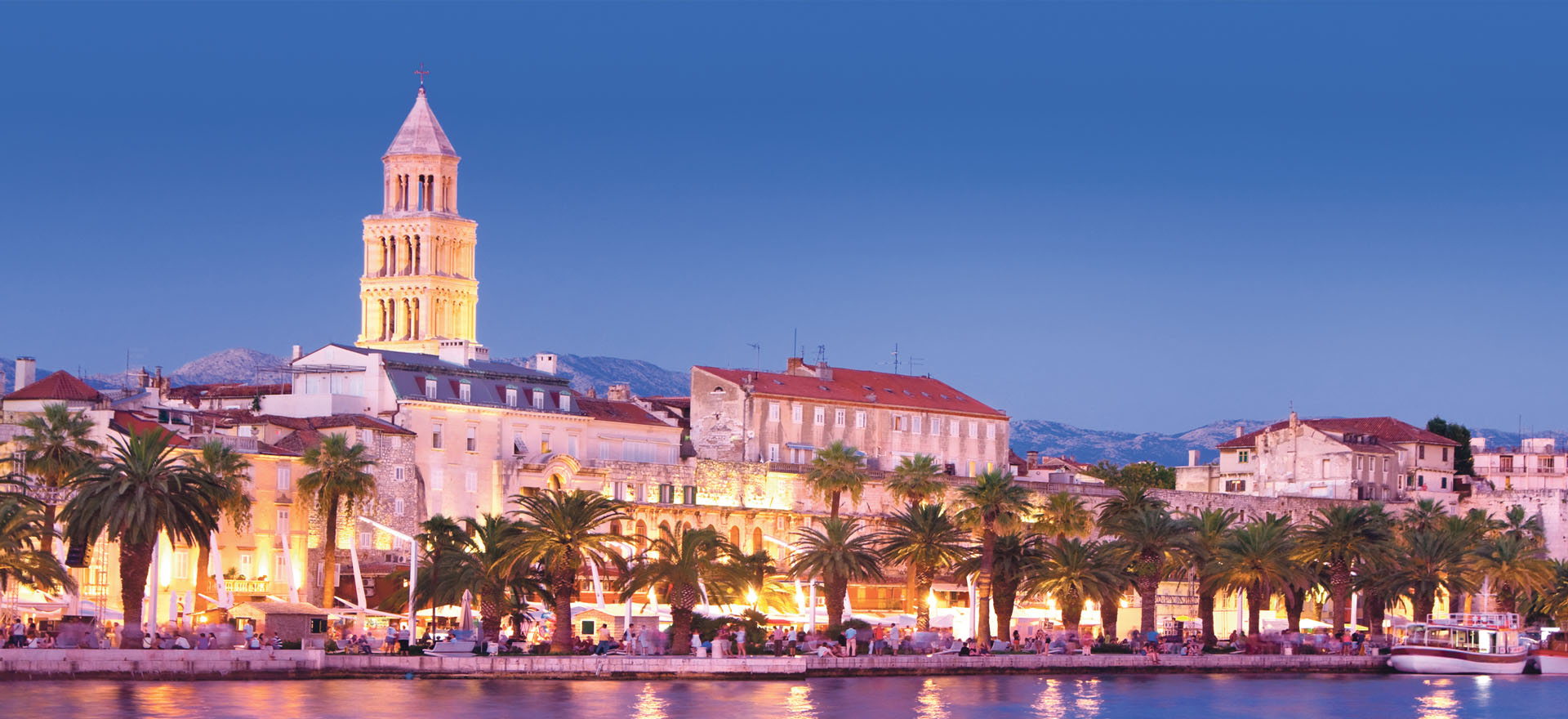 Split waterfront with palm trees in evening