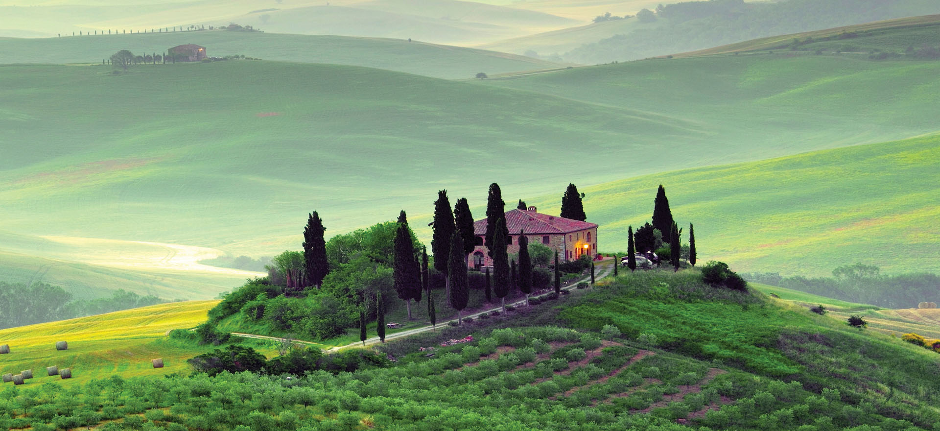 House surrounded by Cypress trees in green Tuscan hills