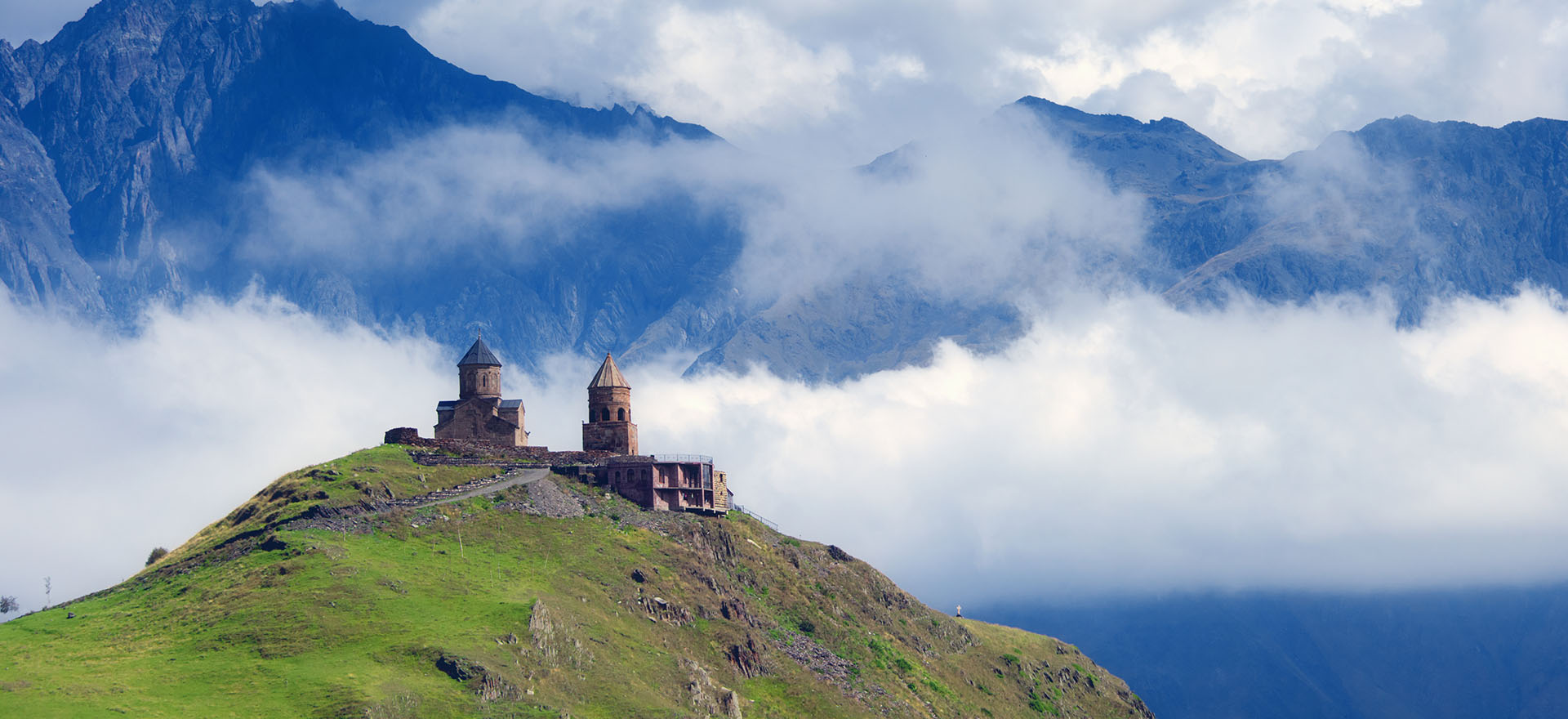 Gergeti Trinity Church on top of caucasus mountains surrounded by clouds