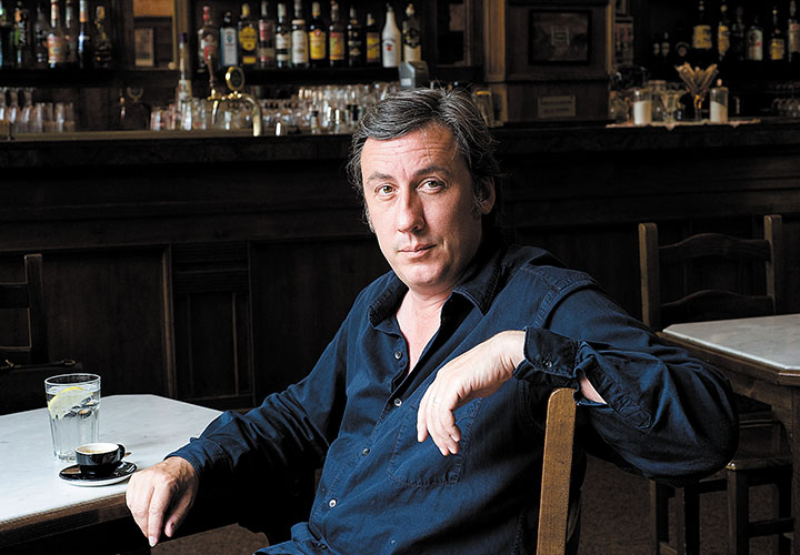 Andrew Graham-Dixon sitting in bar with coffee and water