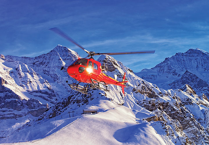 Helicopter flying over the alps