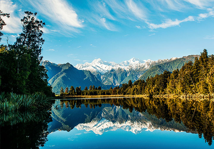 Bright blue lake, fields and mountains in New Zealand