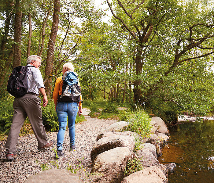 Couple with backpacks walking through trees by river