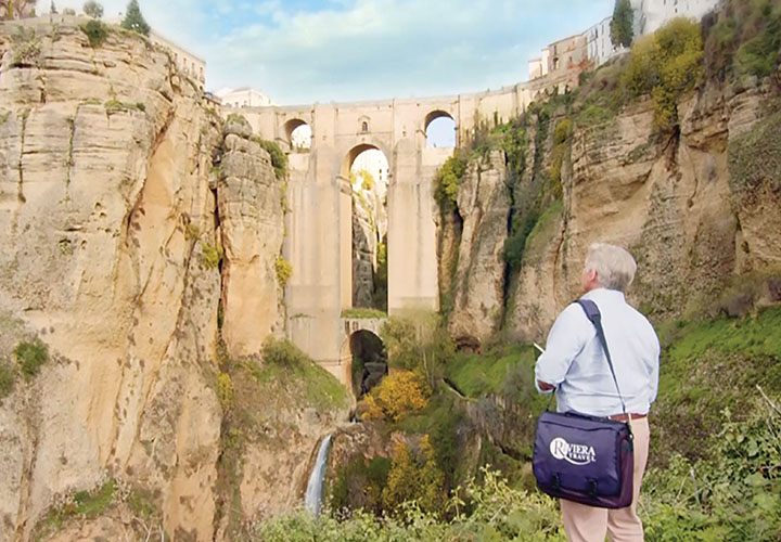 Tour Manager with Riviera Travel bag looking at Puente Nuevo, Ronda