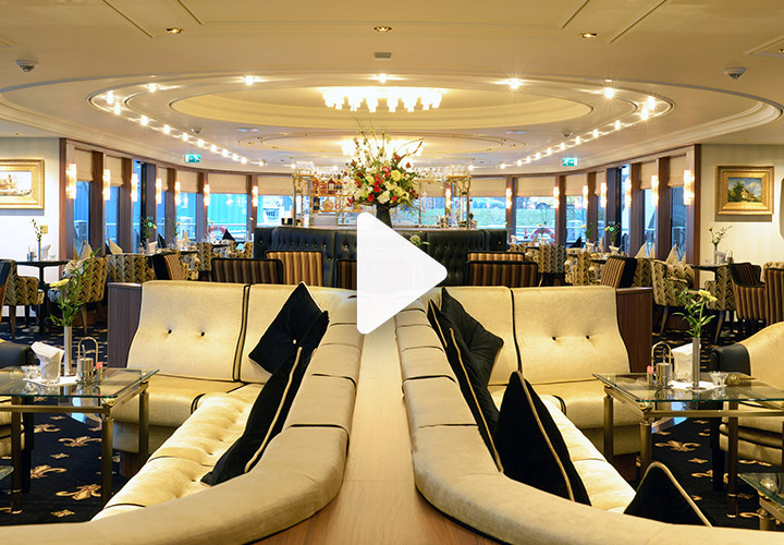 Video play button over ship lounge area with comfy seating