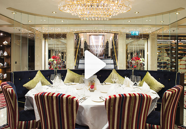 Video play button over ship restaurant table with striped chairs