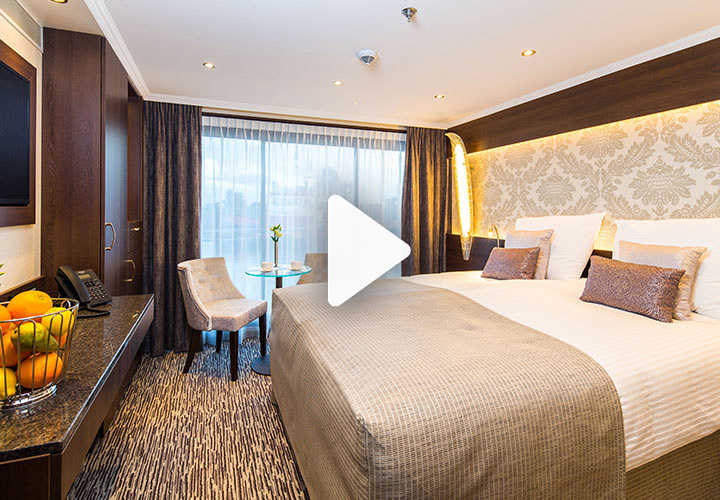 Video play button over spacious suite with double bed and floor to ceiling windows