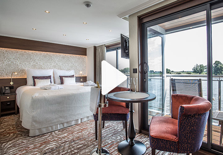 Video play button over large balcony cabin with double bed and floor to ceiling windows