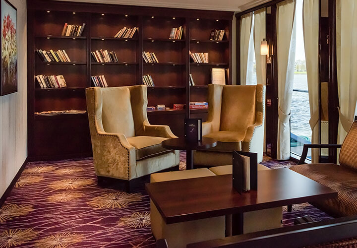 Arm chairs in on-board library, rich wood bookshelves and windows