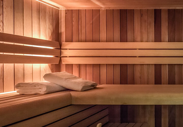 Wood-panelled sauna room with white towels