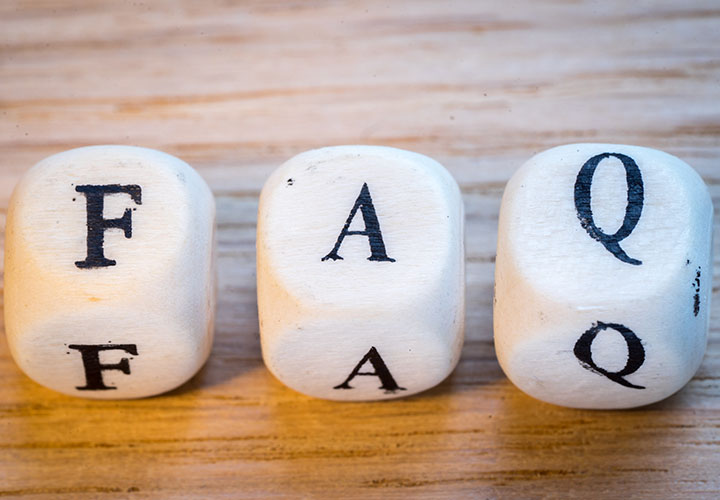 Three white dice with letters FAQ on wooden surface