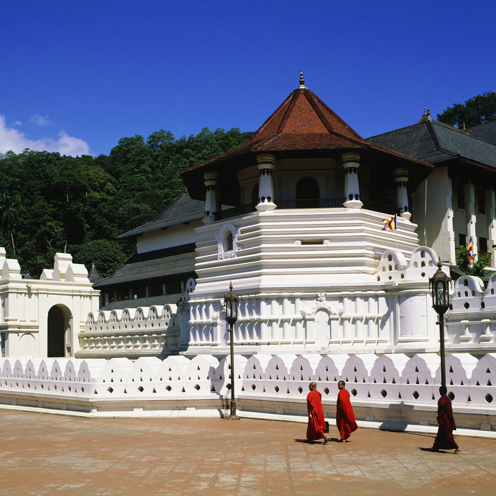 Monks walking past the Temple of the Tooth